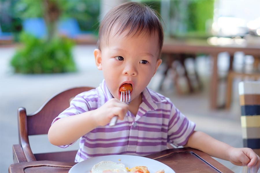 toddler eating a small meatball
