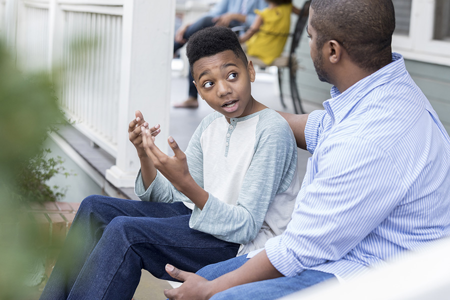 Father talking to teen son about natural consequences of behavior