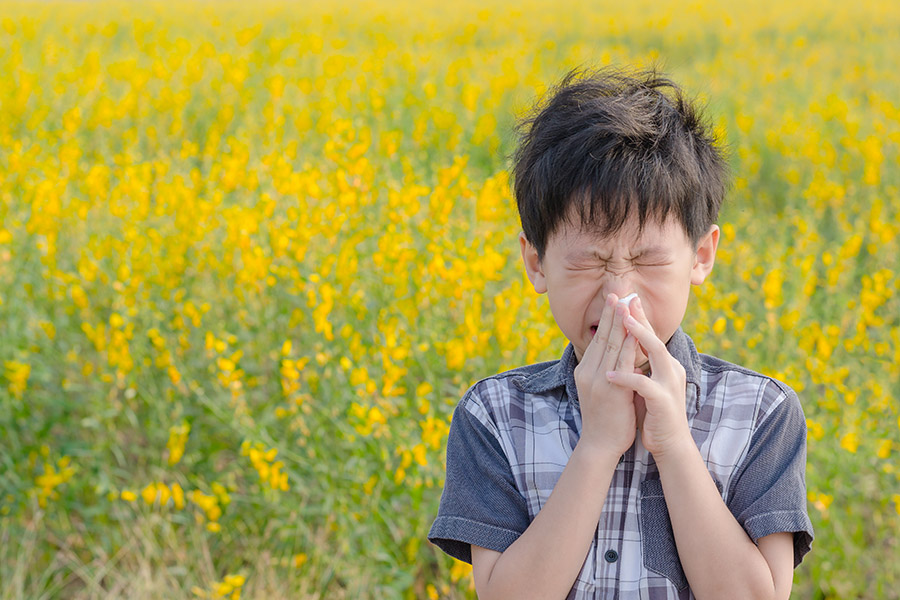 Boy sneezing from allergies